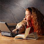 Girl at Laptop Computer with Book And Dog