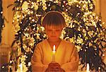 Boy Holding Christmas Candle Near Christmas Tree    Stock Photo - Premium Rights-Managed, Artist: Joel Benard, Code: 700-00017340