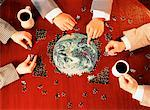 Business People Working on Jigsaw Puzzle of Globe in Boardroom