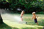 Children in Swimwear, Playing in Sprinkler