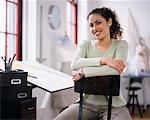 Woman Sitting at Drafting Table Smiling    Stock Photo - Premium Rights-Managed, Artist: Masterfile, Code: 700-00034409