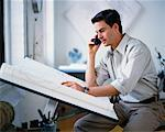 Man Sitting at Drafting Table Using Cell Phone    Stock Photo - Premium Rights-Managed, Artist: Masterfile, Code: 700-00034463