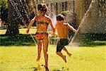 Back View of Boy and Girl in Swimwear, Playing In Sprinkler