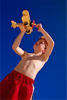 Boy in Swimwear, Playing with Toy Airplane