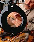 Male Flytier Tying Fishing Fly Under Magnifying Glass