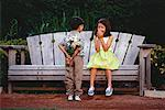 Boy Giving Bouquet of Flowers to Girl Sitting on Park Bench