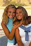 Portrait of Two Teenage Girls on Beach, Smiling