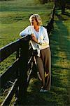 Mature Woman Leaning on Fence Outdoors