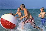 Three Boys in Swimwear, Playing With Beach Ball in Water on Beach