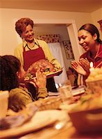 Grandmother Bringing Turkey to Thanksgiving Dinner Table    Stock Photo - Premium Rights-Managednull, Code: 700-00055665