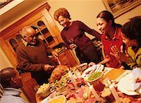 Grandfather Carving Turkey at Thanksgiving Dinner Table    Stock Photo - Premium Rights-Managednull, Code: 700-00055666