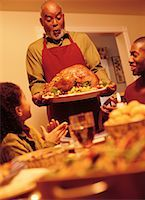 Grandfather Bringing Turkey to Thanksgiving Dinner Table    Stock Photo - Premium Rights-Managednull, Code: 700-00055669
