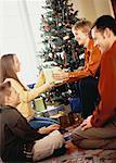 Family Gathered near Christmas Tree, Exchanging Gifts
