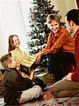 Family Gathered Around Christmas Tree, Exchanging Gifts    Stock Photo - Premium Rights-Managed, Artist: Masterfile, Code: 700-00057510