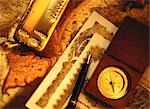 Compass, Pen, Gold Bar and Certificates on Antique World Map