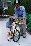 Father and Son Fixing Bicycle Outdoors    Stock Photo - Premium Rights-Managed, Artist: Peter Griffith, Code: 700-00067030