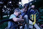 Father and Son Fixing Bicycle Outdoors    Stock Photo - Premium Rights-Managed, Artist: Peter Griffith, Code: 700-00067034