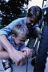 Father and Son Fixing Bicycle Outdoors    Stock Photo - Premium Rights-Managed, Artist: Peter Griffith, Code: 700-00067035