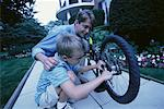 Father and Son Fixing Bicycle Outdoors    Stock Photo - Premium Rights-Managed, Artist: Peter Griffith, Code: 700-00067036