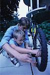 Father and Son Fixing Bicycle Outdoors    Stock Photo - Premium Rights-Managed, Artist: Peter Griffith, Code: 700-00067037