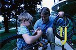 Father and Son Fixing Bicycle Outdoors    Stock Photo - Premium Rights-Managed, Artist: Peter Griffith, Code: 700-00067038