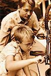 Father and Son Fixing Bicycle Outdoors    Stock Photo - Premium Rights-Managed, Artist: Peter Griffith, Code: 700-00070740