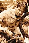 Father and Son Fixing Bicycle Outdoors    Stock Photo - Premium Rights-Managed, Artist: Peter Griffith, Code: 700-00070741