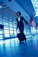 Businesswoman Walking in Terminal Pulling Luggage    Stock Photo - Premium Rights-Managed, Artist: Peter Griffith, Code: 700-00071166