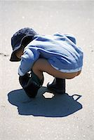 Young Boy Crouching on Beach    Stock Photo - Premium Rights-Managednull, Code: 700-00074125