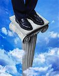 Businessman Standing on Pedestal in Clouds