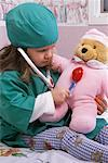 Girl Sitting on Bed in Doctor Costume, Playing Doctor with Teddy Bear