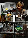 Woman Looking at Fruit Salad in Fridge with Chocolate Cake, Tofu And Juice    Stock Photo - Premium Rights-Managed, Artist: Philip Rostron, Code: 700-00079958