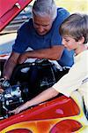 Grandfather and Grandson Working On Engine in Hot-Rod    Stock Photo - Premium Rights-Managed, Artist: Peter Griffith, Code: 700-00086239