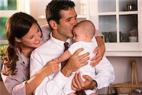 Father Kisses Baby While Mother Watches    Stock Photo - Premium Rights-Managednull, Code: 700-00154884