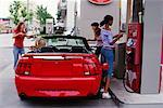 Teenage Girls Putting Gas in Car