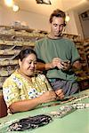 Woman making jewelry and man using pda Stock Photo - Premium Royalty-Free, Artist: Chad Johnston, Code: 604-00231260