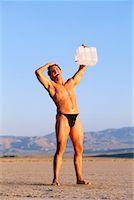 Man in desert with water jug Stock Photo - Premium Royalty-Freenull, Code: 604-00231591