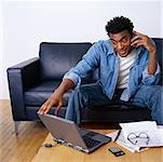 Man Sitting on Sofa Using Laptop And Cellular Phone    Stock Photo - Premium Rights-Managed, Artist: Orbit, Code: 700-00269454