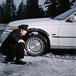 Chauffeur Looking at Wheel of Car Stuck on Ice    Stock Photo - Premium Rights-Managed, Artist: Anthony Redpath, Code: 700-00286666