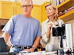 Couple in Kitchen Making Coffee and Looking at Laptop