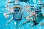 Couple Swimming Underwater in Pool