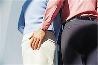 Businessman touching businesswomans bottom Stock Photo - Premium Royalty-Freenull, Code: 614-00394981