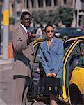businessman holding a cab door open for a woman