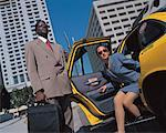 low angle view of a businessman holding a cab door open for a woman