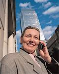 businesswoman talking on mobile standing near office buildings Stock Photo - Premium Royalty-Free, Artist: mocker, Code: 618-00445368