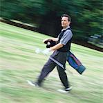 blurred shot of a golfer walking with a golf bag on his shoulder and a golf club in his hand Stock Photo - Premium Royalty-Free, Artist: Cusp and Flirt, Code: 618-00448320