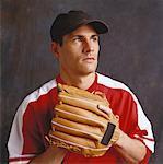 shot of a young man with a baseball cap wearing a baseball mitt Stock Photo - Premium Royalty-Freenull, Code: 618-00448327