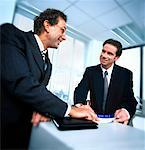 two men talking at a counter Stock Photo - Premium Royalty-Free, Artist: Jon Feingersh, Code: 618-00449318
