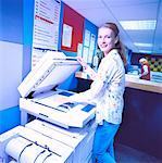 portrait of a young woman at a photocopying machine making photocopies Stock Photo - Premium Royalty-Free, Artist: Masterfile, Code: 618-00449458