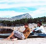 side profile of two young men sitting beside a kayak on the shore